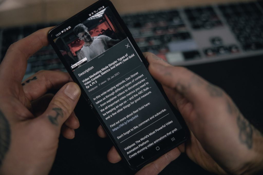Hands holding smartphone, whose screen is showing a video on YouTube