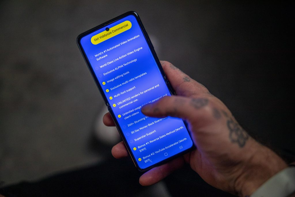 Man with tattooed hands holding a smartphone with Viddyoze checkout on screen