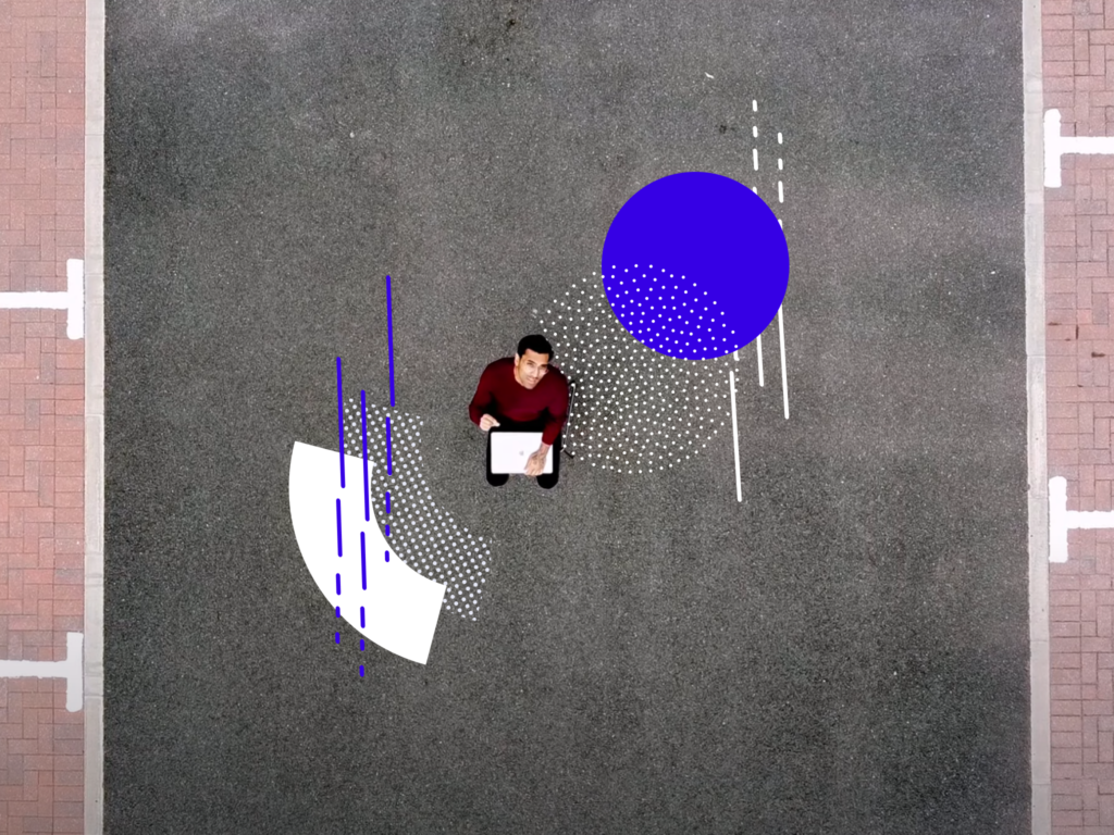 Bird's eye view of a man sitting on a chair outside looking up (for an article on scaling up ads)