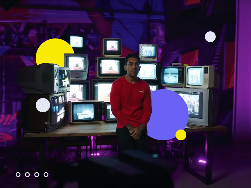 Man in front of a stack of TVs –image being used for an article on paid advertising.